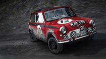 A Mini Cooper S navigates a tight corner in a gravel stage.